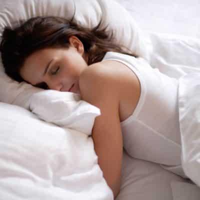 Slapende vrouw op bed